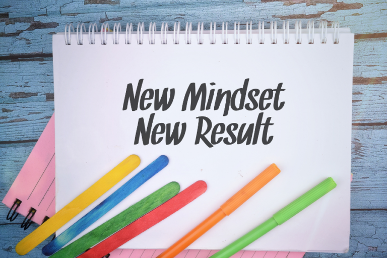 """A notepad with the word """"New Mindset New Result"""" with colored pens."""
